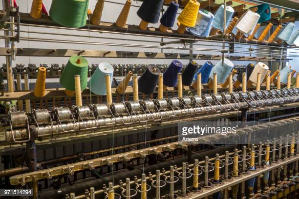 Colourful bobbins with yarns on twisting frame in cotton mill / spinningmill