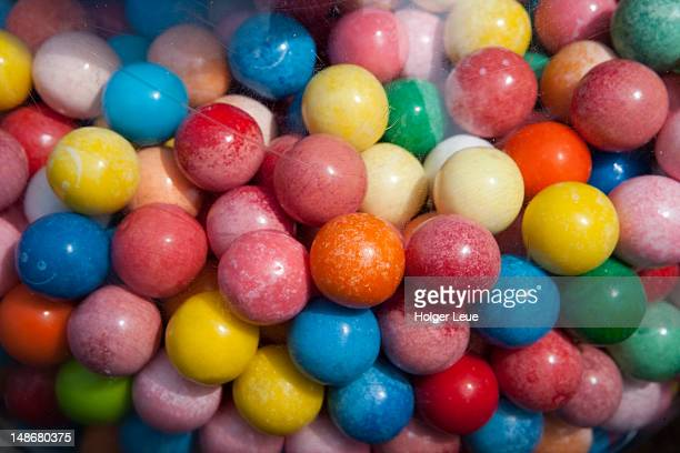 colourful bubble gum balls inside machine. - gumball machine stock pictures, royalty-free photos & images