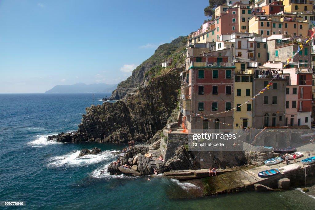 Farbenfrohen Gebäuden und Boote, dramatischen Felsformationen und Menschen entspannen an der Küste von Italien. : Stock-Foto