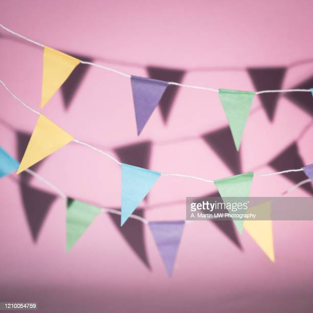 colourful bunting casting shadows on a pink background - bunting stock pictures, royalty-free photos & images