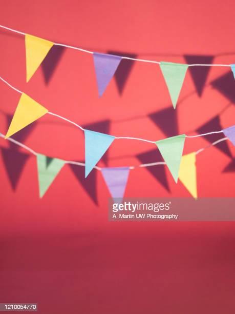 colourful bunting casting shadows on a pink background - aniversario fotografías e imágenes de stock