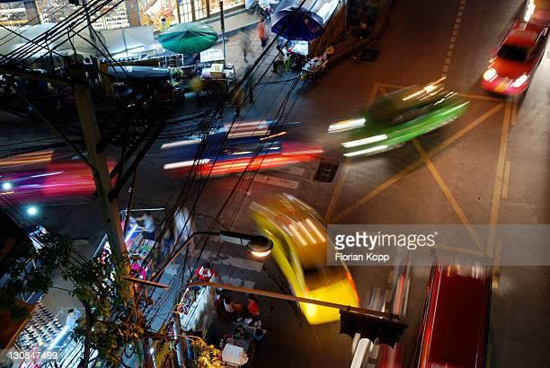 Colourful cars entering a side street of Sukhumvit Road at night, Bangkok, Thailand