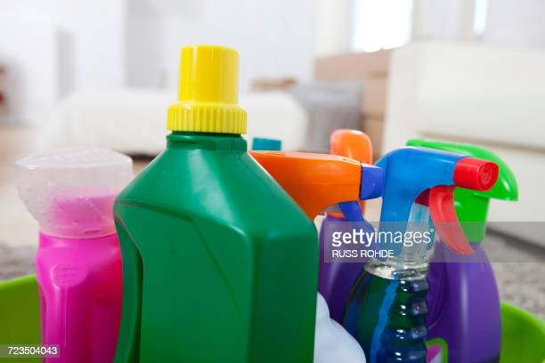 Colourful cleaning product plastic bottles and sprays on kitchen counter