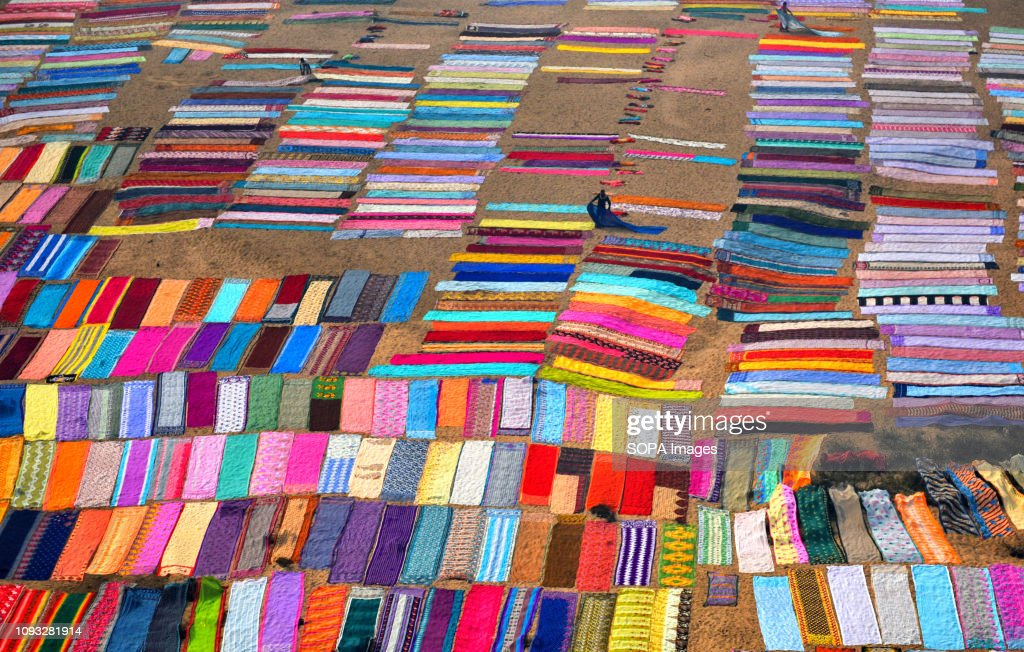Colourful clothes being spread on the soil next to the river... : News Photo