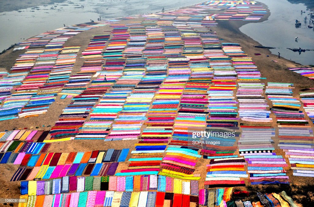 Colourful clothes spread on the soil next to the river bank... : News Photo