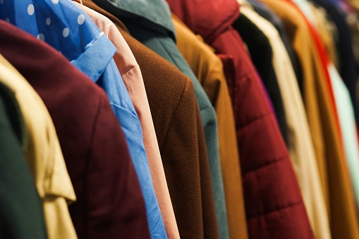 Colourful coats in the charity shop. 875820218