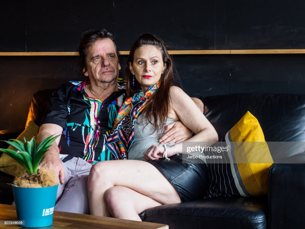 Colourful Couple relax on a lounge in a bar in St Kilda : Stock Photo
