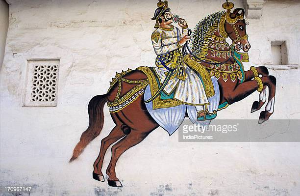 A colourful detailed painting in a courtyard of the City Palace showing a king in ceremonial dress and riding a horse Udaipur Rajasthan India