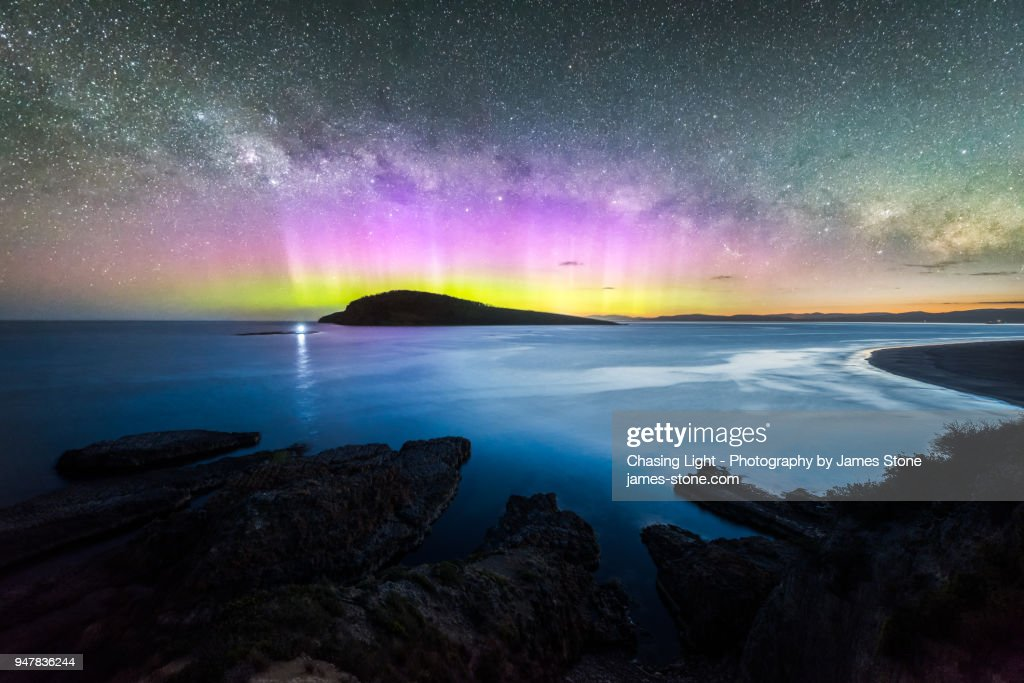 Colourful display of the Aurora Australis over an island in the ocean at Blue Hour : Stock Photo