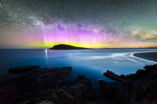 Colourful display of the Aurora Australis over an island in the ocean at Blue Hour - gettyimageskorea