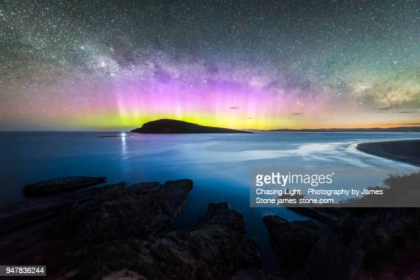 colourful display of the aurora australis over an island in the ocean at blue hour - aurora australis stock pictures, royalty-free photos & images