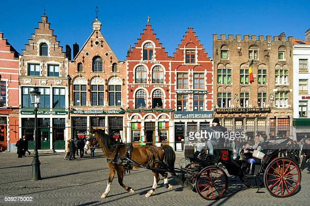 Colourful facades of restaurants and horse pulling coach with tourists at the Market place Bruges West Flanders Belgium