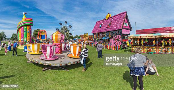 Colourful fairground rides at crowded village summer fair panorama