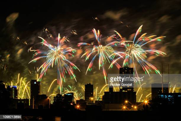 colourful fireworks over city buildings - australia day stock pictures, royalty-free photos & images