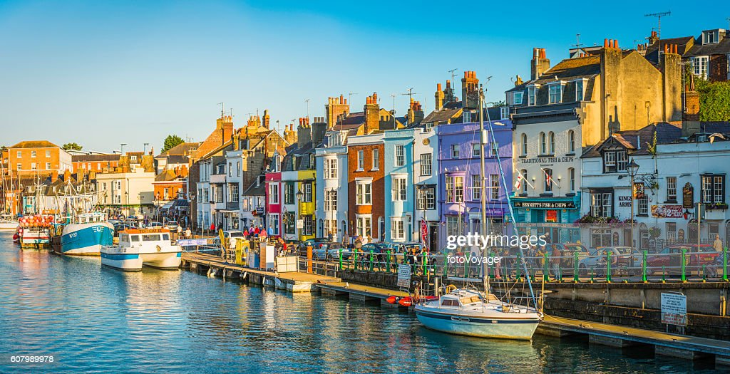 Colourful fishing cottages seaside harbour resort tourists pubs panorama Dorset : Stock Photo