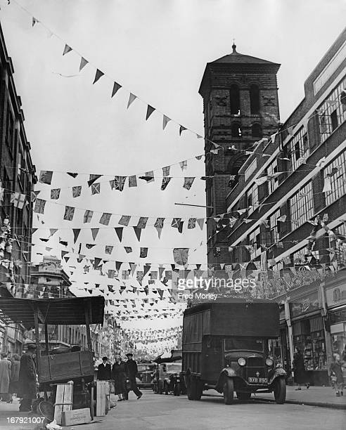 Colourful flags and bunting above Exmouth Street Market in Clerkenwell to celebrate the Coronation London 22nd May 1953