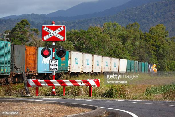 colourful freight train passing protected rural road crossing - railings stock pictures, royalty-free photos & images