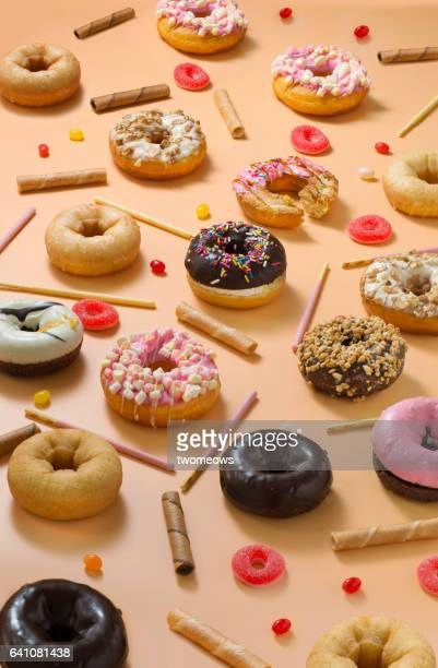 Colourful glazed donuts, candy and snacks on orange background.