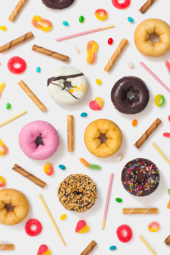 Colourful glazed donuts, candy and snacks on white background. - gettyimageskorea