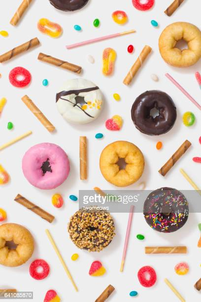 Colourful glazed donuts, candy and snacks on white background.