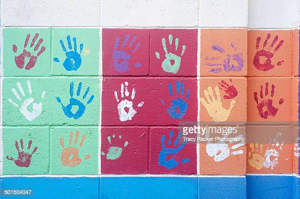 Colourful handprints on a painted wall in Bristol.