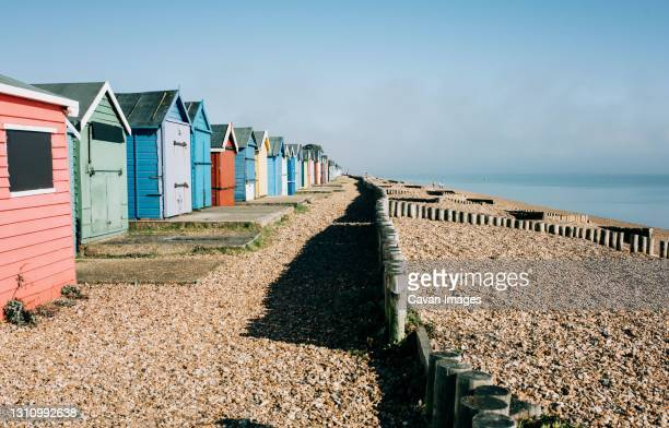 colourful huts on a pebble beach on a sunny day in england - coastline stock pictures, royalty-free photos & images