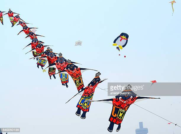Colourful kites flying in clear blue sky, India
