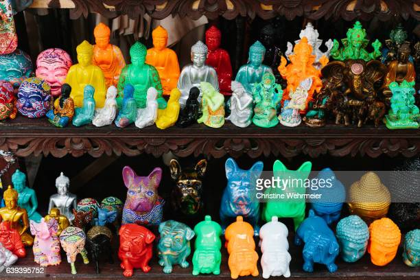 colourful miniature buddhas and dog statues at a souvenir market stall in ubud - ubud district stock pictures, royalty-free photos & images