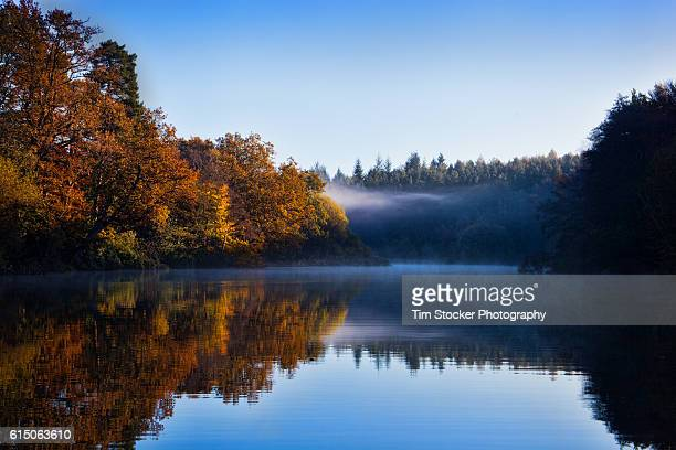 A colourful misty sunrise looking across a blue River with trees in Autumn colours.