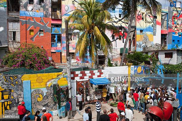 Colourful mural walls at Callejon de Hamel with Sunday afternoon rumba crowd.