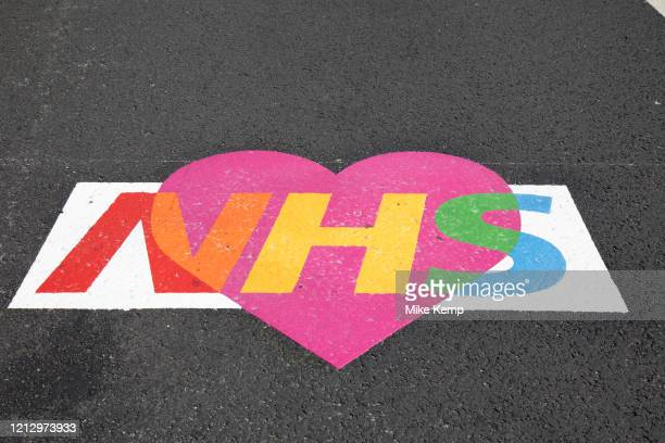 Colourful NHS love heart logo in support of NHS staff and key workers painted onto the street at Westminster as lockdown continues and people observe...