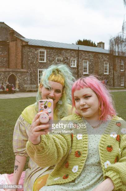 colourful outdoor portrait of a young non-binary couple taking a selfie - human relationship stock pictures, royalty-free photos & images