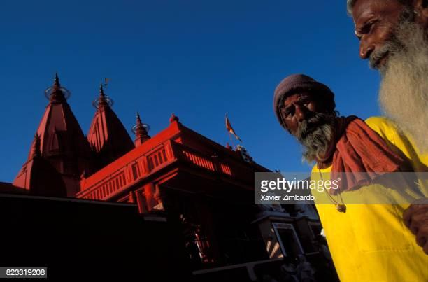 Colourful pilgrims in yellow dress walking near a red temple during Maha Kumbh Mela on April 14 1998 in Haridwar Uttarakhand India
