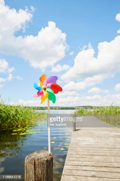 colourful pinwheel toy at a jetty at an idyllic lake against sky - ruhige szene stock-fotos und bilder