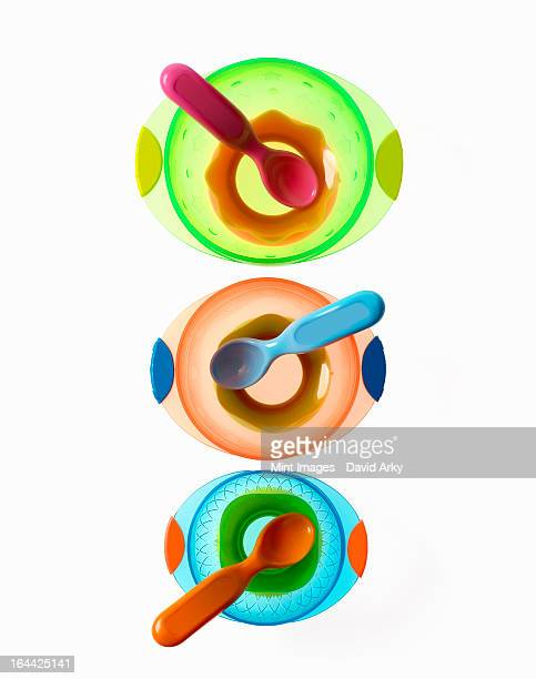 Colourful plastic spoons for use by infants and babies. Coloured plastic bowls.