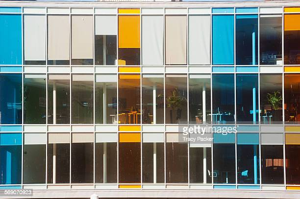 Colourful rectangle panels of turquoise orange glass punctuate the window facade of this modern office development at the base of the Shot Tower...