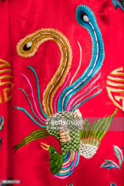 Colourful red Chinese embroidered silk garment depicting a phoenix bird for sale China
