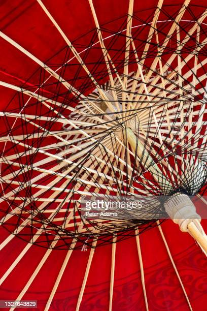 colourful red sun parasol at street market in bagan, mandalay region, myanmar - peter adams stock pictures, royalty-free photos & images