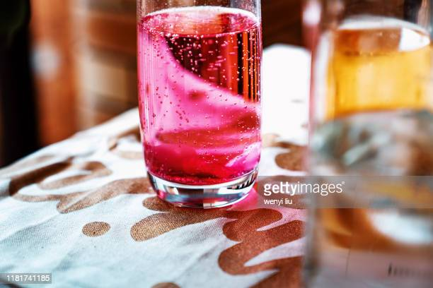 colourful sparkling water in the glass on a table cloth with golden letters - carbonated water stock pictures, royalty-free photos & images