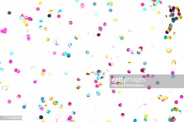 colourful sparlking confetti on white background - karneval stock-fotos und bilder
