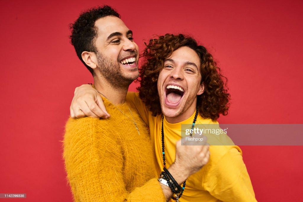 Colourful studio portrait of a gay male couple : ストックフォト
