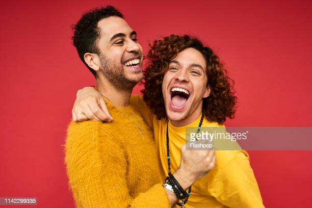 colourful studio portrait of a gay male couple - gender identity stock pictures, royalty-free photos & images