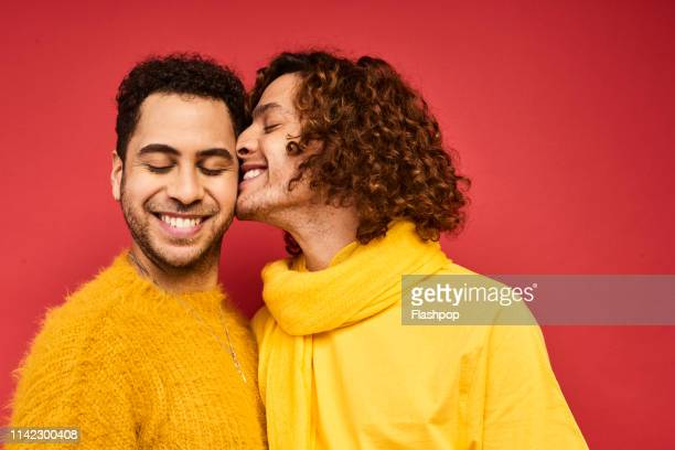 colourful studio portrait of a gay male couple - couple photos et images de collection