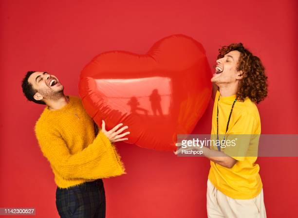 colourful studio portrait of a gay male couple - gay love photos et images de collection