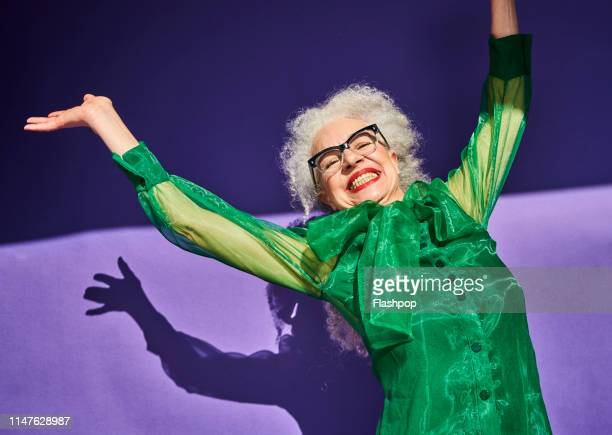 colourful studio portrait of a senior woman - senior women stock pictures, royalty-free photos & images