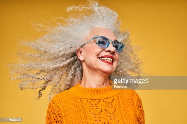 colourful studio portrait of a senior woman - orange farbe stock-fotos und bilder