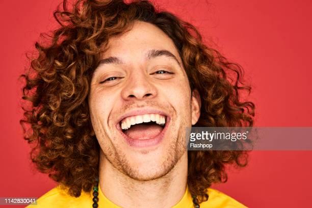 colourful studio portrait of a young man - offenes lächeln stock-fotos und bilder