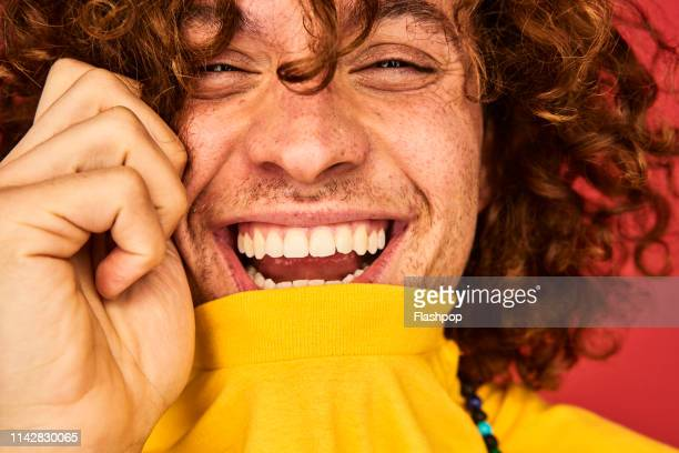 colourful studio portrait of a young man - lachen stockfoto's en -beelden