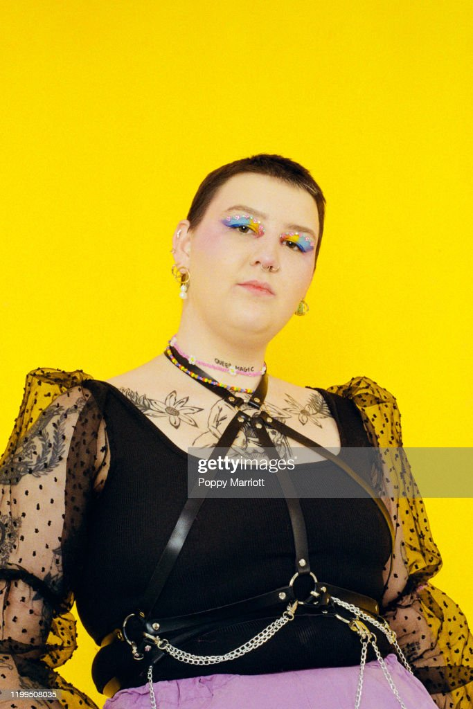Colourful studio portrait of a young non-binary individual : Stock Photo