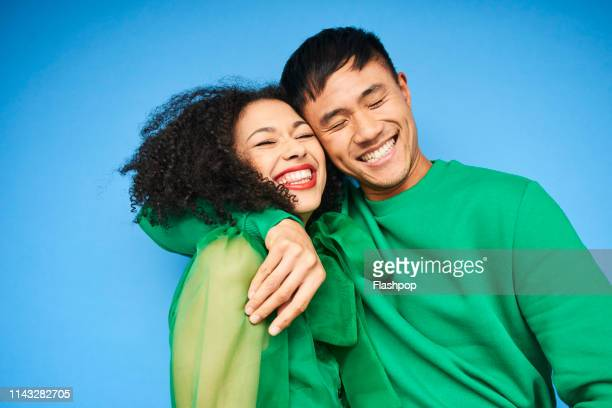 colourful studio portrait of a young woman and man - sfondo a colori foto e immagini stock